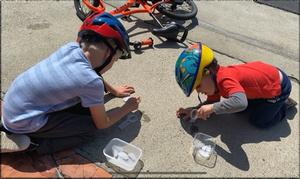 Boys melting ice on the sidewalk