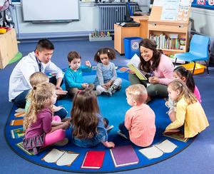 Kindergarten class sitting in a circle on a blue carpet