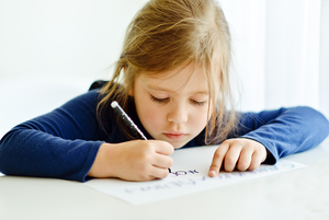 Elementary age girl writing with a pencil
