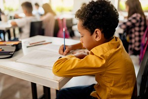 elementary boy student writing in a classroom