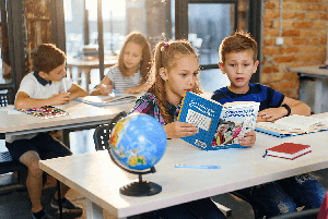 Elementary students reading iCivics Reader in classroom