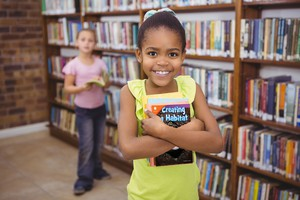 A smiling girl holding books in a school library